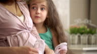 Young pregnant woman and her little daughter play with tiny booties. Slow motion. video