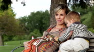Young pregnant woman with son sitting on a bench video