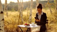 Young pretty business woman using tablet park video