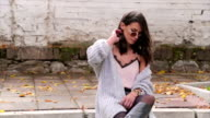Young pretty fashioned girl siting on the street. video