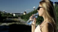 Young pretty woman drinks water Bottle of spring water video