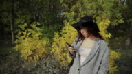 Young pretty woman in black hat and glasses received a SMS with a very good news video