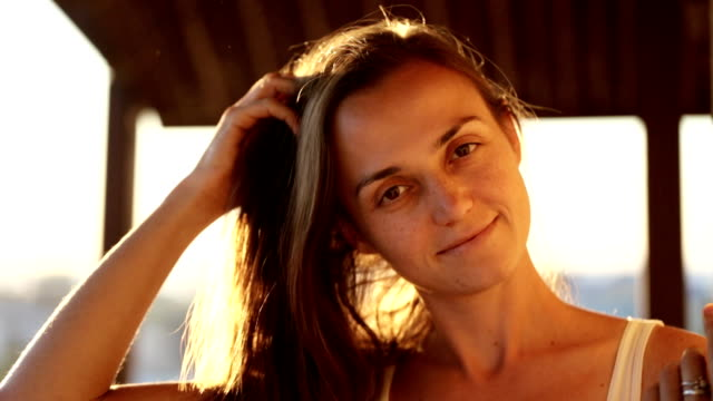 Young pretty woman smiling and looking at camera on the balcony at sunset. video