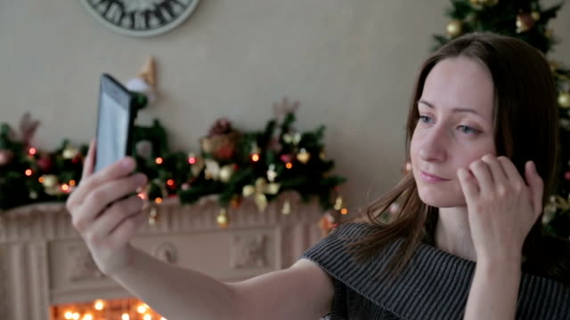 Young pretty woman taking selfie at home while sitting near Christmas tree video