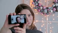 Young pretty woman taking selfie at home while sitting near Christmas decor video