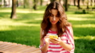 Young pretty woman write sms on phone against background of summer park video
