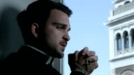 young priest praying with a rosary in his hands: bell tower in background video