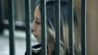 young prisoner behind bars thinks sadly to her fate video