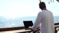 Young professional businessman using modern laptop outdoors video