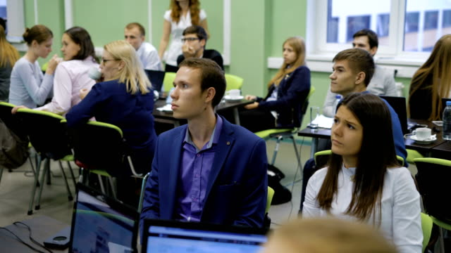 Young professionals in the audience of the institution in the training business. Teams taking part in the training carefully listening to the opponents video