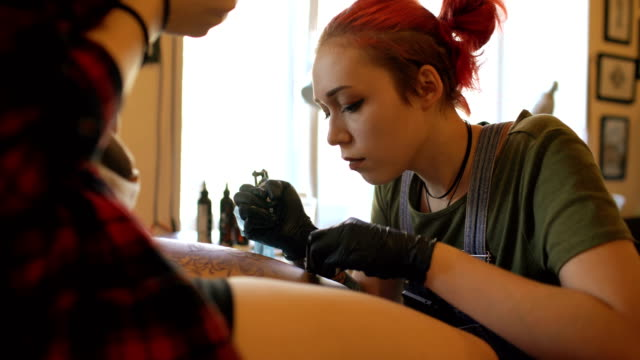 Young red haired woman tattoo artist tattooing picture on leg of young girl client in studio video