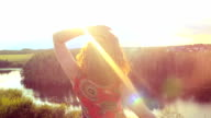 Young red-haired curly haired woman standing on rock looks at sun and raising hands in feeling happiness video