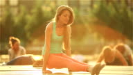 Young red-haired woman practicing yoga in a city park. in the rays of the setting sun. video