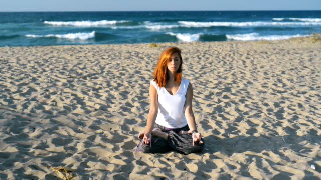 Young redhead woman at early 30s meditating on the beach I video