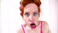 Young Redhead Woman Curlers In Hair Pulling A Face video