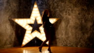 young rock guitarist, dances. shining star in the background. slow motion, silhouette video