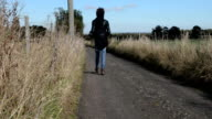 Young rock musician walks lonely country road video