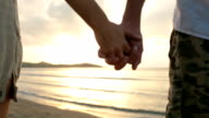Young romantic couple hold hands at sunset on shore in summer outdoor - gimbal steadicam HD video footage video