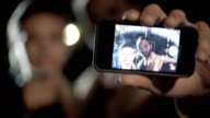 Young romantic couple in love makes a selfie outdoor at night, focus on smarthphone - slow-motion HD video footage video
