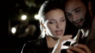 Young romantic couple in love smile, laugh using smartphone outdoor at night - slow-motion HD video footage video