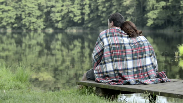 Young romantic couple in nature seated on lake jetty look at panorama in summer day outdoor - HD video footage video