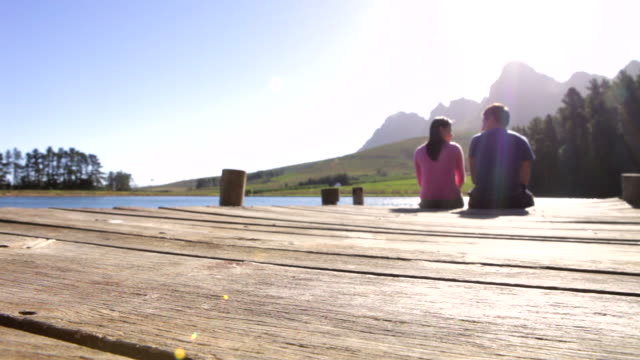 Young Romantic Couple Sitting On Jetty Looking Out Over Lake video