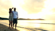 Young romantic couple walk at sunset on shore in summer outdoor - gimbal steadicam HD video footage video