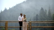 Young romantic pair - pretty girl in long light dress and handsome man kissing and hugging on bridge in the forest video