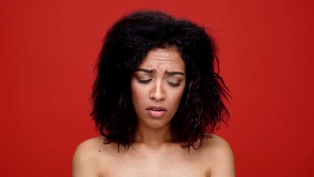 Young sad african woman says no over red background. video