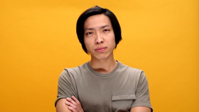 Young sad asian man says no isolated over yellow background. video