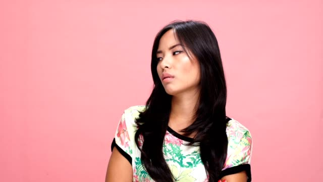 Young sad asian woman says no over pink background. video