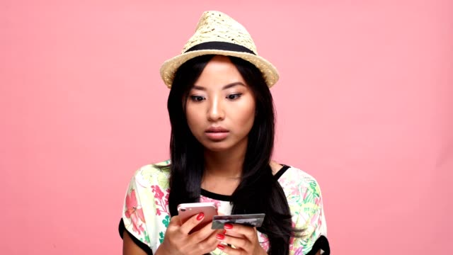 Young sad asian woman wearing hat holding credit card and using phone over pink background. video