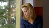 Young sad woman looking out the window and waiting video