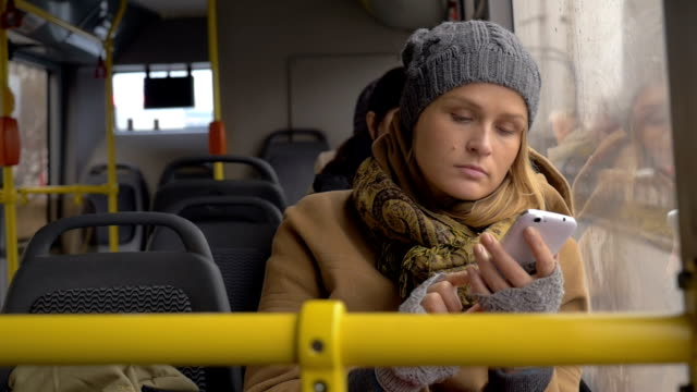 Young sad woman using smart phone in the bus video