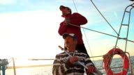 Young sailor and senior captain on sailboat, teamwork, help video