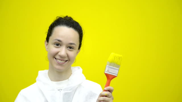 Young satisfy smiling girl gesturing with yellow brush video HD video