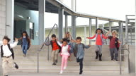 Young school kids jumping down steps as they leave school video