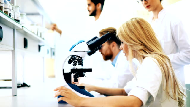 Young scientist looking through microscope in laboratory video