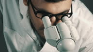 Young scientist looking through the microscope video
