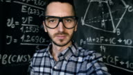 Young scientist man making selfie shoot in chemical and mathematical equations wall room interior video