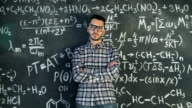 Young scientist man posing in chemical and mathematical equations wall room interior video