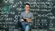 Young scientist man read book in chemical and mathematical equations wall room interior video