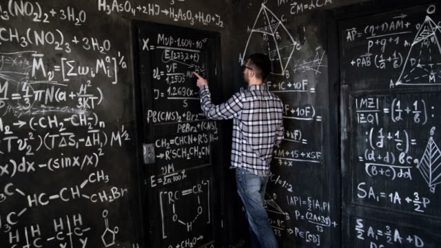 Young scientist man write chock in chemical and mathematical equations wall room interior timelapse video