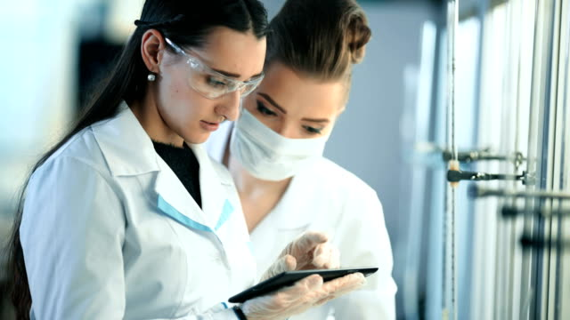 Young scientists with tablet pc making test or research in clinical laboratory video