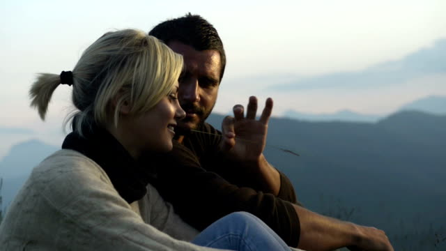 Young seated couple whatch panorama mountain at sunset video HD video