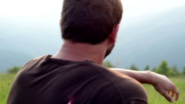 Young seated man watch at panorama on mountain video HD video