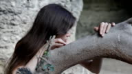 Young seductive girl near tree trunk video