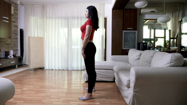 Young sexy attractive woman watching TV fitness tutorial exercising in the living room at home video