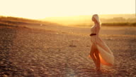 Young sexy beautiful girl with long hair in a beautiful dress walks on lyazhu at sunset dress develops in the wind video