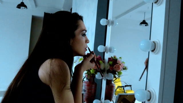 young Sexy brunette paints her lips with a pencil near the mirrors video